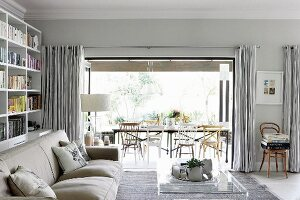 Pale sofa and transparent coffee table in modern living room with rustic ambiance; open folding doors with view of long table and chairs in background