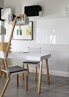 Avant-garde chairs around table and shelf mounted on wooden pole, framed picture and floating shelves in background