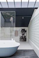 Elegant minimalist bathroom with glass-brick wall and designer bathtub