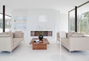 Open fireplace, white floor and glass walls in designer lounge
