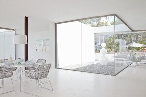 View from bright dining area to white sculpture in atrium with floor-to-ceiling glass walls