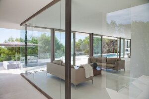 View of elegant living area, terrace and pool through glass walls