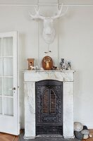 Stag's head on wall above marble fireplace with iron firebox and animal figurines on mantel