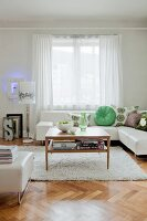 White leather sofa with patterned scatter cushions, wooden table with magazine shelf and green glass vase in living room