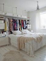 Lacy blanket on double bed in front of open clothes rail and storage boxes in feminine bedroom