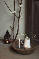 Christmas arrangement: old wooden dish, candles, jug of twigs, lantern and branch decorated with bows of wool on wooden floor