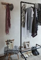 Warm slippers below clothing hanging from vintage clothes rack, rustic wall hooks and lamp with knitted lampshade on child's chair
