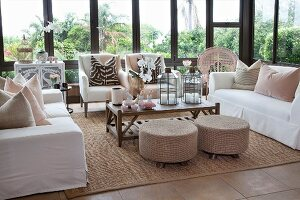 Comfortable lounge area in conservatory: sofas with white loose covers, arranged scatter cushions and pouffes around coffee table
