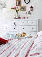 A breakfast tray and a red and white patterned duvet with a simple, country house-style white chest of drawers in the background