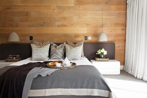 Double bed with grey covers, upholstered headboard, scatter cushions and throws in bedroom with wood-clad wall