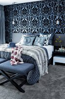 Ornate wallpaper and scatter cushions on double bed in bedroom with dark colour scheme