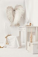 Chair with white loose cover at rustic writing desk; decorative angels wings on wall in background