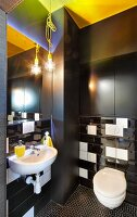 Modern toilet with black installations, black and white glossy wall tiles and yellow accents