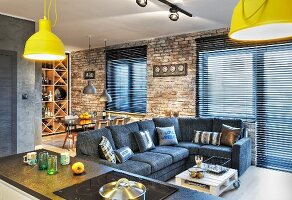 Grey sofa, dining area and wine rack in open-plan interior with brick wall and closed louvre blinds