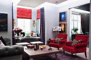 Armchairs with red velvet covers and wooden table in traditional living room with window seat in window bay