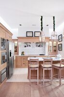 Bar stools and pale wooden counter in open-plan kitchen in modern, country-house style