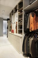 Jackets on clothes racks and drawers in walk-in wardrobe