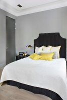 Double bed with dark headboard and scatter cushions arranged on white bedspread in bedroom with walls painted paint grey and traditional ambiance