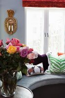 Vase of roses on side table next to curved bench with arranged scatter cushions in front of window