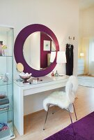 A chair with a white fur cover and a make-up table against a wall with a round mirror on a purple circle