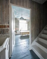 View past white staircase through open door into large bathroom with free-standing bathtub
