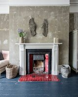 Artwork on wall above open fireplace with red tiles set in slate grey wooden floor; patinated walls