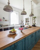Vintage metal pendant lamps above free-standing kitchen counter with blue, patinated base units and oak worksurface