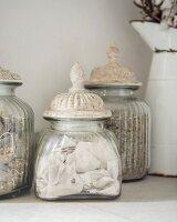 Vintage jars with patinated lids and enamel jug in background