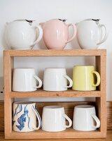 Retro teapots and mugs on wooden shelves
