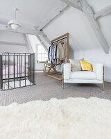 Bedroom in converted attic with retro designer armchair and clothes rail