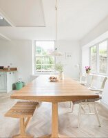 Dining table, bench and white chairs in open-plan light-flooded kitchen-dining room