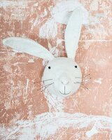 Felt rabbit against wall with dusky pink patinated paint