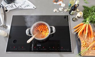 A carrot medley in a steaming pot on an induction stove surrounded by ingredients and cooking utensils