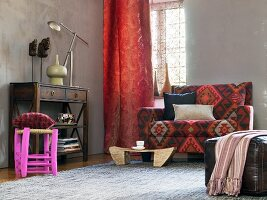 African-style living area - sideboard, red curtains, patterned sofa and leather pouffe