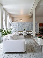 White sofa on simple wooden floor in front of dining area against partition