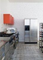 Küchenbereich mit Edelstahl Küchenzeile, oberhalb rot lackierte Hängeschränke, im Hintergrund Kühlschrankkombination