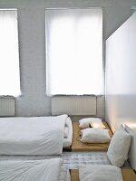 Schlafbereich in japanischem Stil, weisse Vorhänge am Fenster, weiss gestrichene Ziegelwand