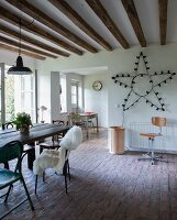 Vintage chairs on paved floor in dining area and star-shaped lamp on wall next to open doorway in rustic interior