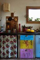 Quirky kitchen counter with floral curtains and doors decorated with old sacks