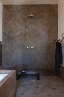 Ethic-style shower with grey-rendered walls and running water