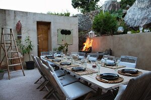 Set table in twilit courtyard of Mediterranean bungalow