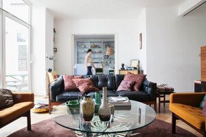 Round glass table, armchairs and leather couch in open-plan interior
