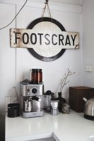Vintage train station sign above various coffee machines on kitchen counter