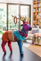 Artistic animal figurine covered in colourful wool on surface
