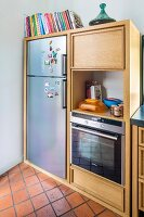Pale wooden kitchen units with integrated fridge and oven