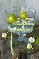 Green apples and ox-eye daisies in bowl of water decorated with green gingham ribbon on vintage wooden bench