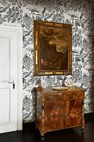 Antique, carved cabinet and framed painting on wallpaper with large botanical print
