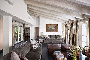 Grey couch and ottomans in seating area of open-plan interior with white-painted wooden ceiling