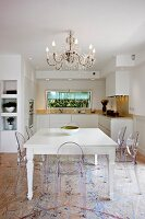 Ghost chairs around white, country-house-style dining table below chandelier in open-plan kitchen