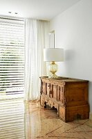 Table lamp with white lampshade on antique, carved wooden cabinet in corner of living room with marble floor